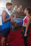 Side view of female athlete holding dumbbells while talking with male royalty free stock photos