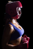 Side view of female boxer with headgear and gloves Royalty Free Stock Images