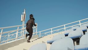 Side view of female fitness coach running up the stairs outdoors before workout slow motion