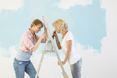 Side view of female friends painting together in new home Royalty Free Stock Photography