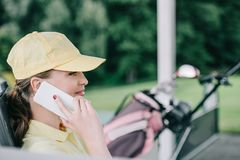 Side view of female golf player in cap talking on smartphone. At golf course stock photo