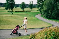 side view of female golf player with golf gear talking on smartphone while walking