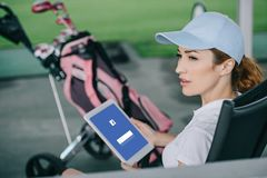 side view of female golf player with tablet with facebook logo on screen in hands royalty free stock image