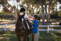 Side view of female jockey assisting sister. Sitting on horse Royalty Free Stock Images