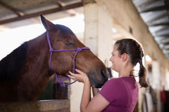 Side view of female jockey holding horse head Stock Photography