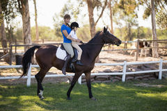 Side view of female jockey teaching horseback riding to girl. At paddlock Stock Image