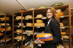 Side view of female salesperson holding cheese in store Stock Photo