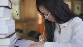 Side view of female student is making notes sitting in university library. Side view of female student is making notes sitting in university library, attractive stock video footage
