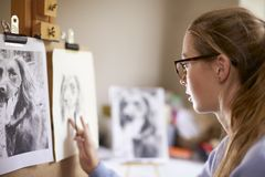 Side View Of Female Teenage Artist Sitting At Easel Drawing Picture Of Dog From Photograph In Charcoal stock photos
