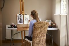 Side View Of Female Teenage Artist Sitting At Easel Drawing Picture Of Dog From Photograph In Charcoal royalty free stock photography