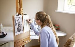 Side View Of Female Teenage Artist Sitting At Easel Drawing Picture Of Dog From Photograph In Charcoal stock images