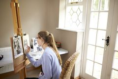 Side View Of Female Teenage Artist Sitting At Easel Drawing Picture Of Dog From Photograph In Charcoal stock image