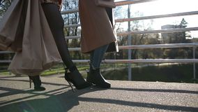 Side view of females legs walking on bridge. Side wiew of sexy females legs walking on pedestrian bridge at sunset. Low section of young women with shoppping stock footage