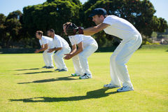 Side view of fielders bending while standing at field. On sunny day royalty free stock photography