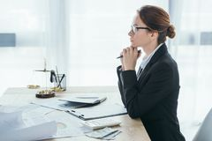 Side view of financier sitting at table. In office stock photo