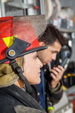 Side View Of Firefighter At Fire Station. Side view of female firefighter at fire station with male colleague in background royalty free stock photography