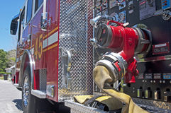 Side view of a firetruck. Up close view of a yellow fire hose and gauges on a firetruck Stock Photos