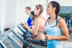 Side view of a fit happy woman and her training group on treadmill royalty free stock photo