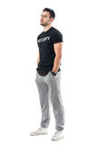 Side view of fit masculine sporty man with hands in pockets looking away. Full body length portrait isolated on white studio background Stock Photos