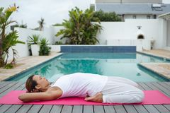 Fit woman performing yoga near swimming pool in the backyard. Side view of fit mixed-race woman performing yoga pose near swimming pool in the backyard. Summer stock photography