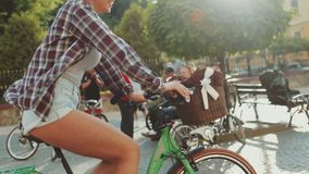 Side view of a fit, sexy blonde woman in casual shirt and jeans shorts riding the vintage bicycle in the historical city stock video