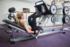 Side view of fit woman doing leg presses in gym Stock Image