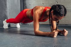 Side view of fit woman doing plank core exercise. Side view of fit woman doing plank core exercise stock images