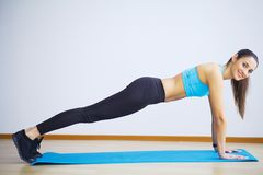 Side view of fit woman doing plank core exercise. stock images
