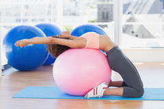 Side view of a fit woman exercising on fitness ball at gym Royalty Free Stock Image