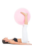 Side view of a fit woman exercising with fitness ball Royalty Free Stock Images