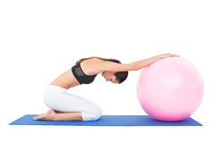 Side view of a fit woman exercising with fitness ball Stock Images