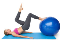 Side view of a fit woman exercising with fitness ball Royalty Free Stock Photography