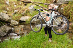 Side view of a fit woman lifting her bike Stock Photos