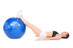 Side view of fit woman lying working out with exercise ball Royalty Free Stock Image