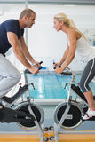 Side view of fit working on exercise bikes at gym Stock Photography