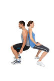 Side view of a fit young couple doing squats Royalty Free Stock Photos