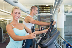 Side view of a fit young couple working on x-trainers at the gym Stock Photos