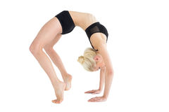 Side view of a fit young woman doing the wheel pose stock photo