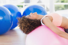 Side view of a fit young woman exercising on fitness ball Royalty Free Stock Photography