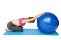 Side view of a fit young woman exercising with fitness ball Royalty Free Stock Photography