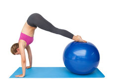 Side view of a fit young woman stretching on fitness ball Royalty Free Stock Images