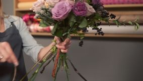 Side view of a flower shop assistant tying a bunch of flowers holding them in hands with the ribbon. Slowmotion shot stock video footage