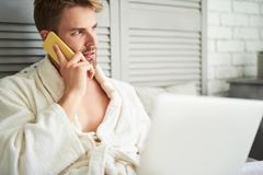 Young male talking on phone after shower. Side view of focused man speaking on mobile. He is sitting on bed in white bathrobe with laptop on knees and listening Stock Photos