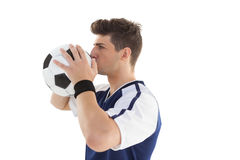 Side view of a football player kissing ball stock photo