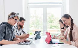Dedicated young people sharing a desk while telecommuting. Side view of four dedicated young people sharing a desk while telecommuting in a modern co-working royalty free stock photography
