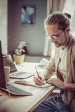 Side view of freelance man sitting at wooden table writing in no Royalty Free Stock Images