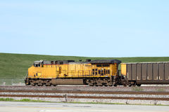 Side view of a freight train. Yellow locomotive and freight train Stock Image