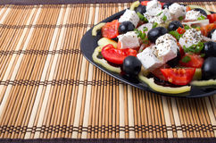 Side view of fresh vegetarian salad on a black square plate Stock Images