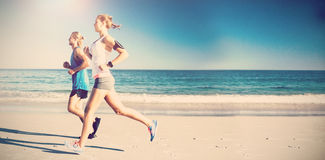 Side view of friends jogging at beach Stock Photos