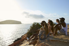 Side View Of Friends Sitting On Cliff Watching Sunset Royalty Free Stock Images